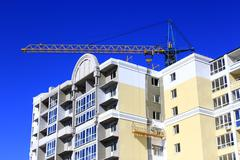 Construction of multistorey modern house with hoisting crane Stock Photos