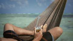 Man drinks beer in hammock Stock Footage