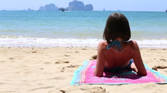 Young girl raises on elbows on towel tans Stock Footage