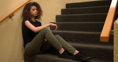 Sad and depressed young girl sitting in stairwell 4k - stock footage