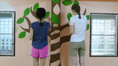Short-Term Missions Team Painting Wall Mural In School Stock Footage