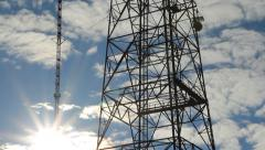 Communication towers. Silhouetted by sun. Time lapse clouds. - stock footage