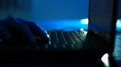 Male hands typing on laptop computer at night - stock footage