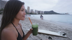 Woman surfer drinking green vegetable smoothie Stock Footage