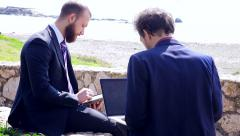 Two business men working with ipad and Macbook Pro in front of the beach Stock Footage