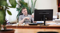 Adult Caucasian man employee sitting with cellphone, swiping the screen, reading Stock Footage
