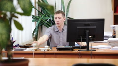 Busy white collar worker answering with two telephones while sitting at desk in  Stock Footage