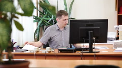Caucasian office manager starting to work with paper documents at desk Stock Footage