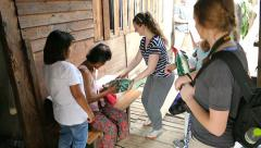 Short-Term Missions Team Giving Rice To Elderly Woman In Slum Stock Footage