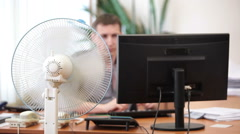 Office heat with cooling fan and perspiring white collar worker leaving his work Stock Footage