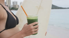 Green detox smoothie - woman drinking vegetable juice on beach after surfing Stock Footage