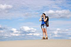 Beautiful girl with camera hiking in desert Stock Photos