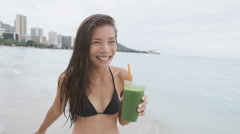 Green detox cleanse vegetable smoothie bikini girl smiling happy on beach - stock footage