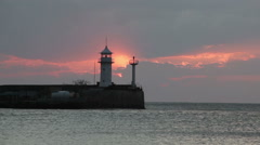 Stock Video Footage of Sunrise over the Black Sea against a beacon in Yalta,  Crimea