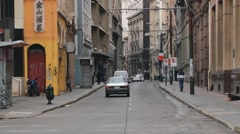 People pass by the street of the historic quarter in Valparaiso, Chile. Stock Footage