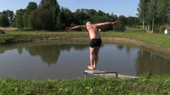 Middle-aged man make head jump into pond water from bridge Stock Footage
