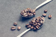 Coffe beans in steel spoons on black Stock Photos