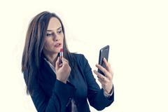 Beautiful woman making up using her phone like a mirror Stock Photos
