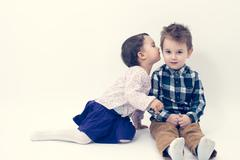 little girl kissing her older brother on the cheek isolated - stock photo
