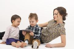 Young mother with two children watching cartoons on cell phone on a white bac - stock photo