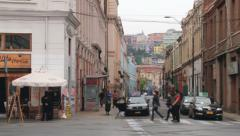 People pass by the street of the historic quarter in Valparaiso, Chile. - stock footage