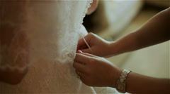 Girlfriends help the bride to wear a wedding dress Stock Footage