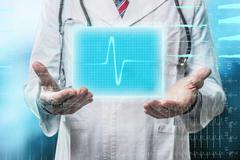 doctor with futuristic heart hologram - stock photo