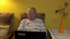 Elderly woman using laptop computer - stock footage