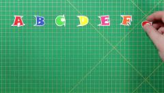 Alphabet beying spelled out on the green background Stock Footage