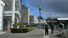 New Zealand Auckland people walk toward Sky Tower past planters 4k 1 Stock Footage