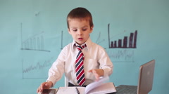 Smart little boy, working on a computer and talkin on the phone Stock Footage
