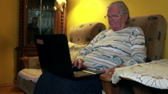 Elderly woman tries to use laptop computer - stock footage