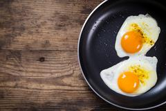 Two frying eggs in pan on table Stock Photos
