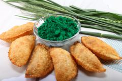 Gujia in plate with holi green color in bowl Stock Photos