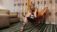 Cute young woman wearing leg warmers and high heels talking to camera Stock Footage
