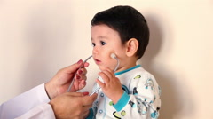 CLOSE UP-HANDHELD SHOT. Child holds a stetoscope during a medical check up. Stock Footage