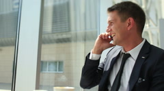 Laughing man talking on the phone in the cafe Stock Footage