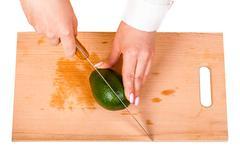 chef cuts the avocado - stock photo