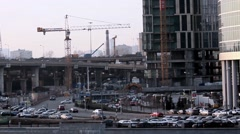 Cars pass by a large business trade center, a crane is working on the building Stock Footage