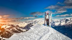 Girl in top of the mountain on skis in hand Stock Photos