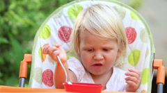 Little girl sits in  chair and eats mango with spoon Stock Footage