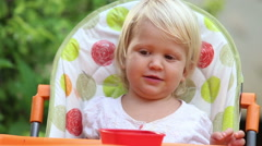 Little girl sits in  chair and eats mango and play pranks Stock Footage
