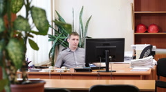 Lazy white collar worker laying back on chair and idly looking at monitor screen Stock Footage