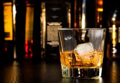Whiskey glass with ice in front of bottles Stock Photos