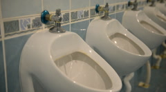 Interior of public men room with white urinals and tiles - stock footage
