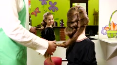 Braid hair for a little girl in a beauty salon Stock Footage