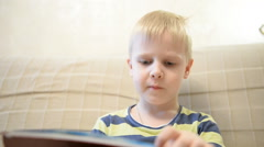 Boy 5 years reading a book at home on the couch - stock footage