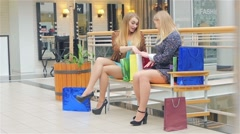 Two young women sitting with shopping bags and smiling. Slow motion Stock Footage
