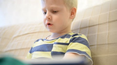 Boy 5 years reading a book at home on the couch Stock Footage