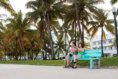 Female Asian Tourists People Watch Along Miami Beach Recreational Area Stock Photos